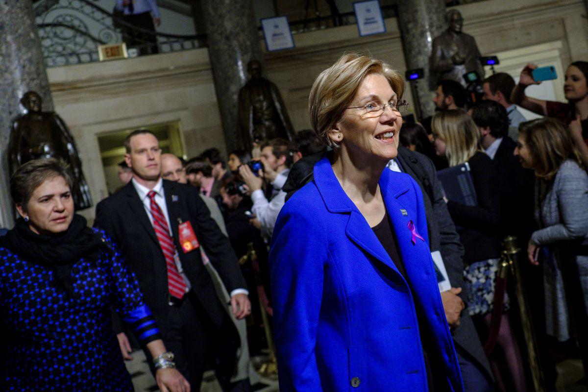 Sen. Elizabeth Warren (D-MA), wearing a purple ribbon, makes her way to State of the Union.