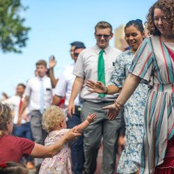 A member of the Utah provo Mission high-fives a child during the Grand Parade in Provo on Monday, July 5, 2021.