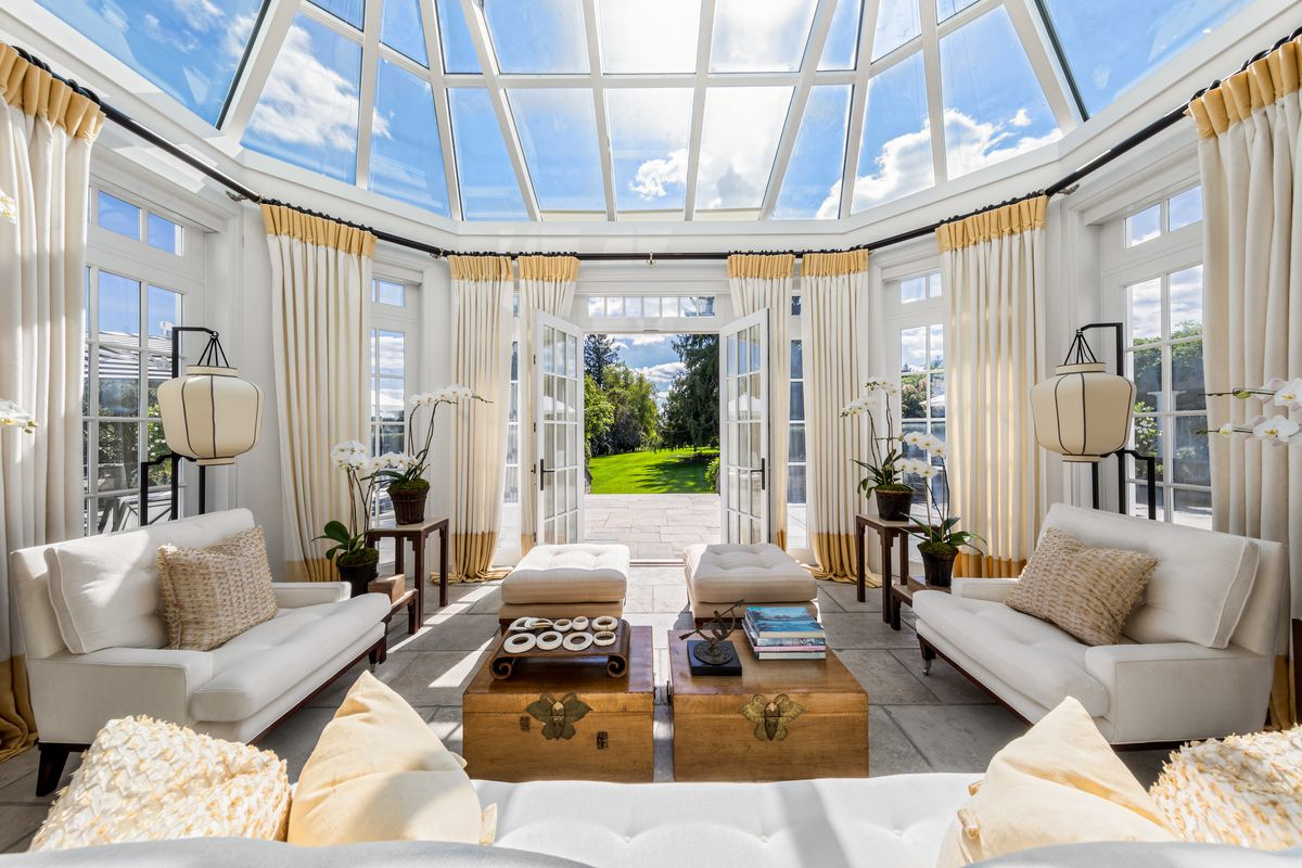 A sun room with glass walls and a rounded glass ceiling is surrounded by white curtains and white furniture. An open French door leads to a bluestone patio.