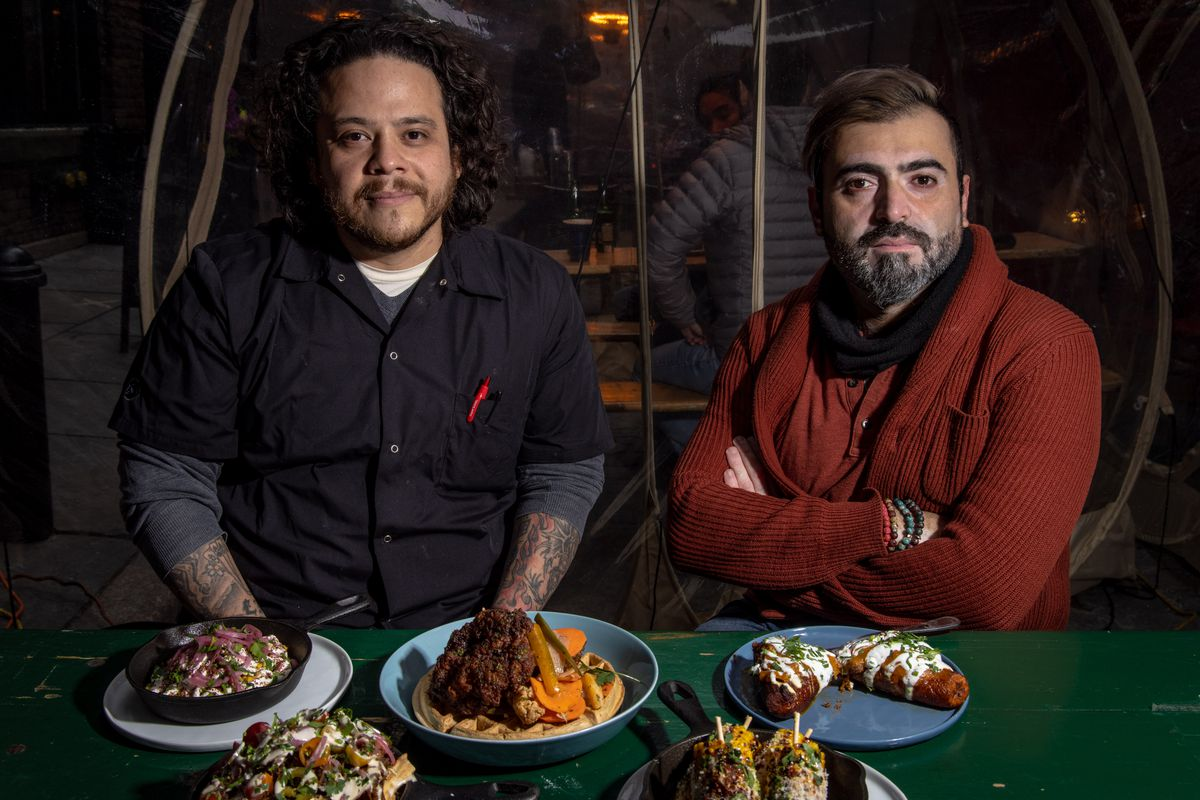 Co-chef Dan Dorado, clad in a black button down and Chef-owner Nasser Jaber, in a chunky red knit cardigan sit in front of a spread of dishes at a green outdoor table