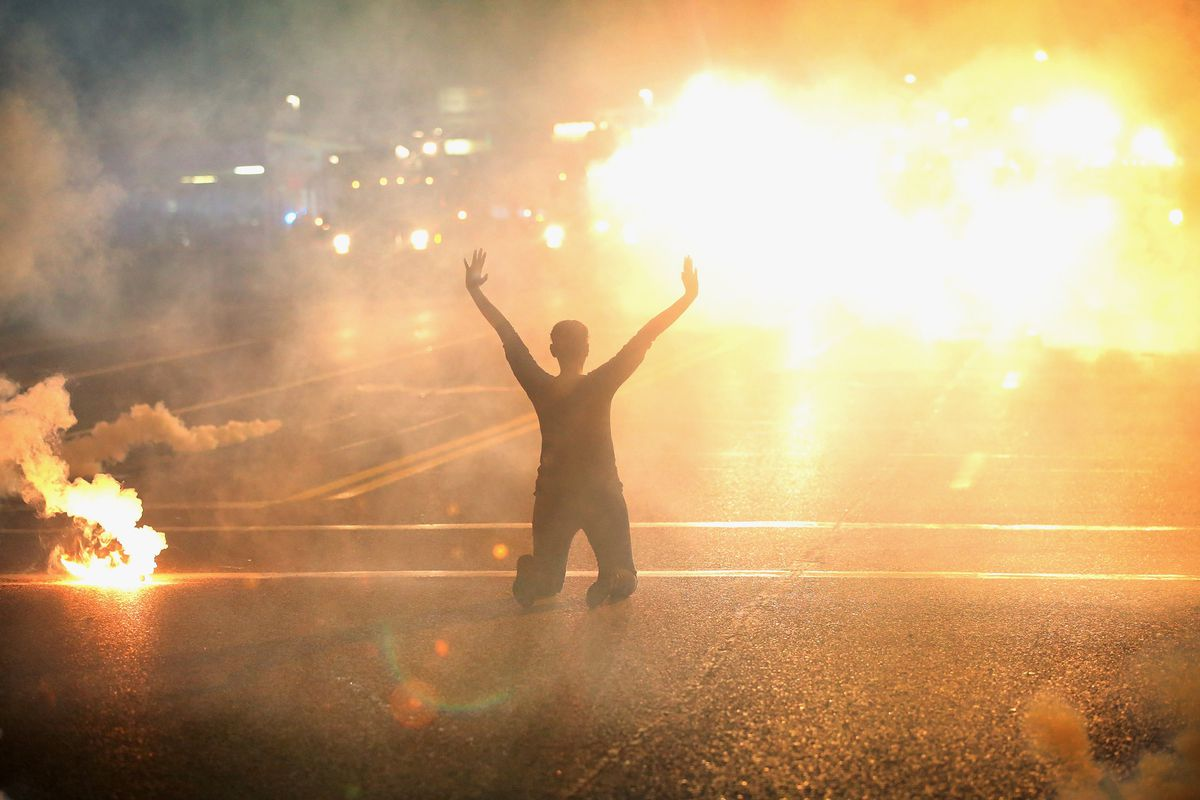 A protester in Ferguson, Missouri, kneels while surrounded by tear gas.