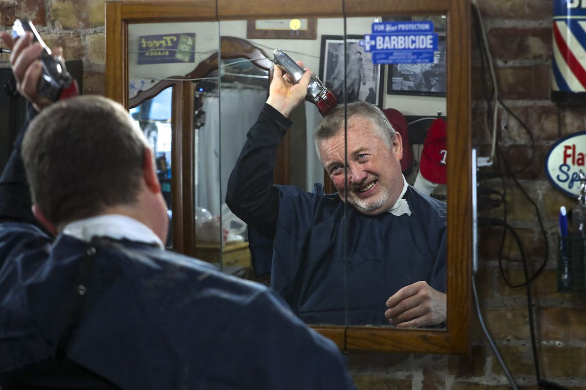 Perry's Barber Shop owner Perry Knuth cuts his own hair in his empty shop in downtown Salt Lake City on Wednesday, April 29, 2020. After being closed for several weeks, Knuth was in his shop for a trim and to clean before possibly reopening as COVID-19 restrictions are eased on May 1.