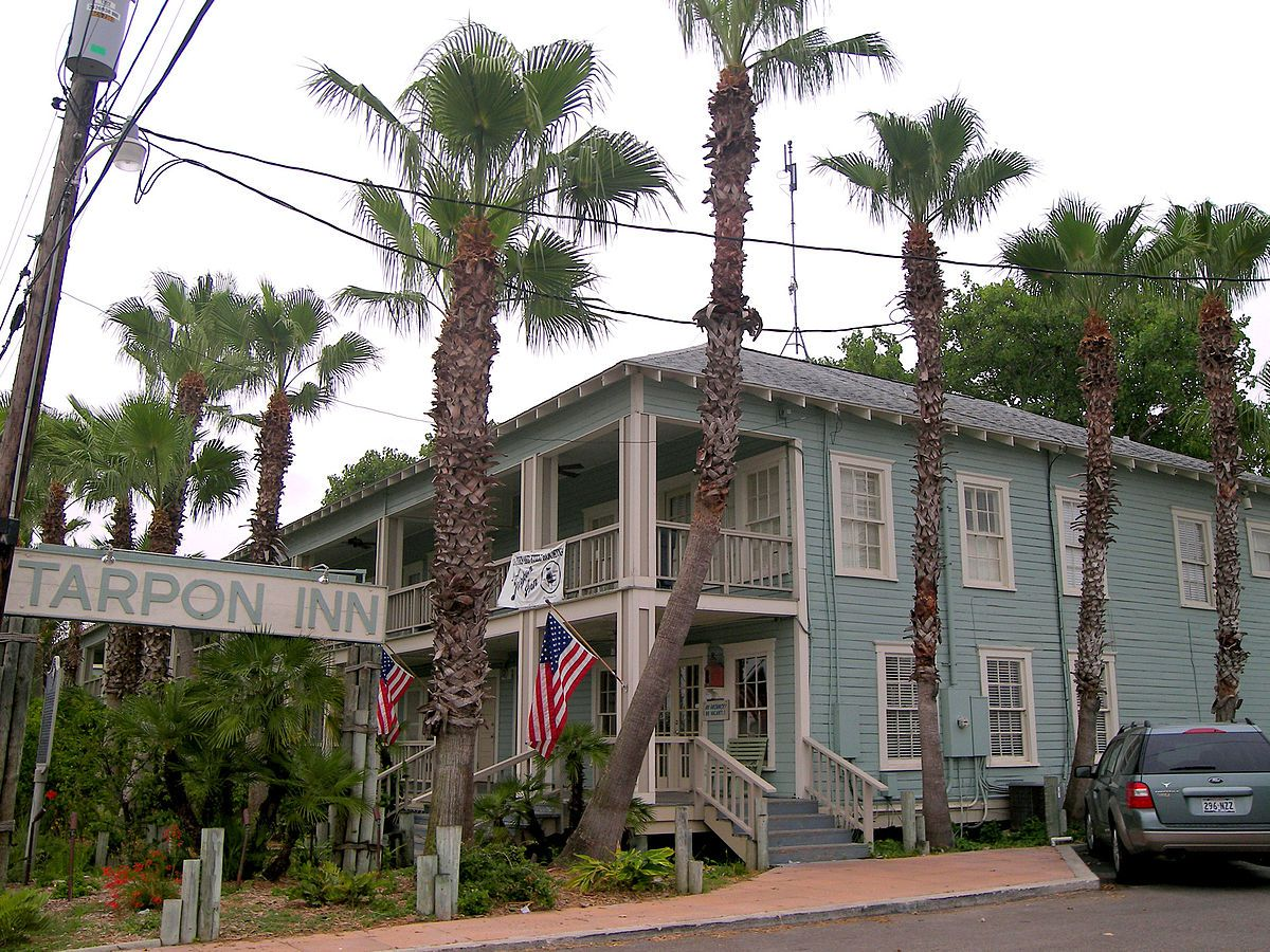 The exterior of the Tarpon Inn in Texas. The facade is blue with a white wraparound porch. There are palm trees in front.