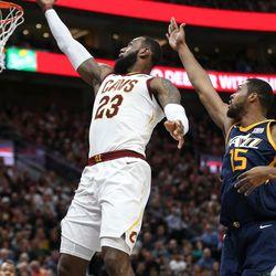 Cleveland Cavaliers forward LeBron James (23) puts the ball in ahead of Utah Jazz forward Derrick Favors (15) at Vivint Arena in Salt Lake City on Saturday, Dec. 30, 2017.