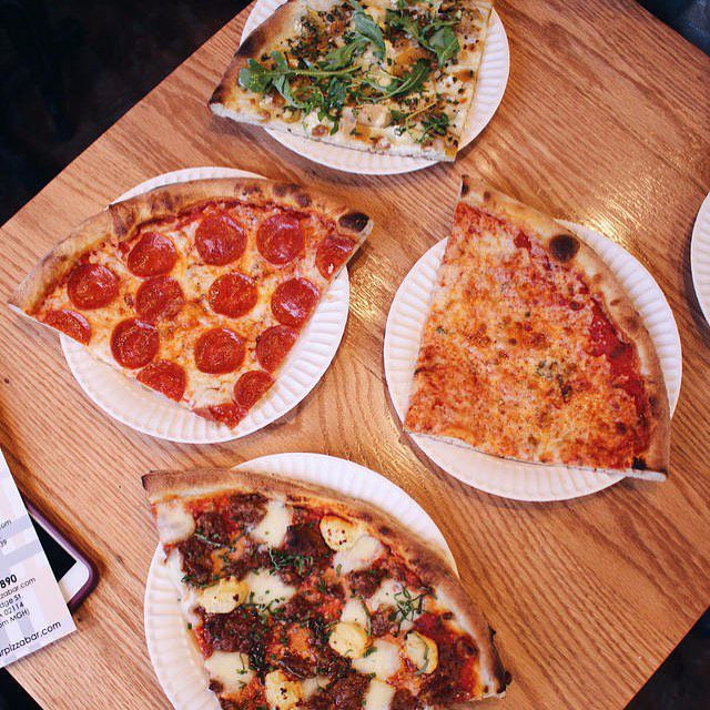 Overhead view of several different types of pizza slices on white paper plates on a wooden table