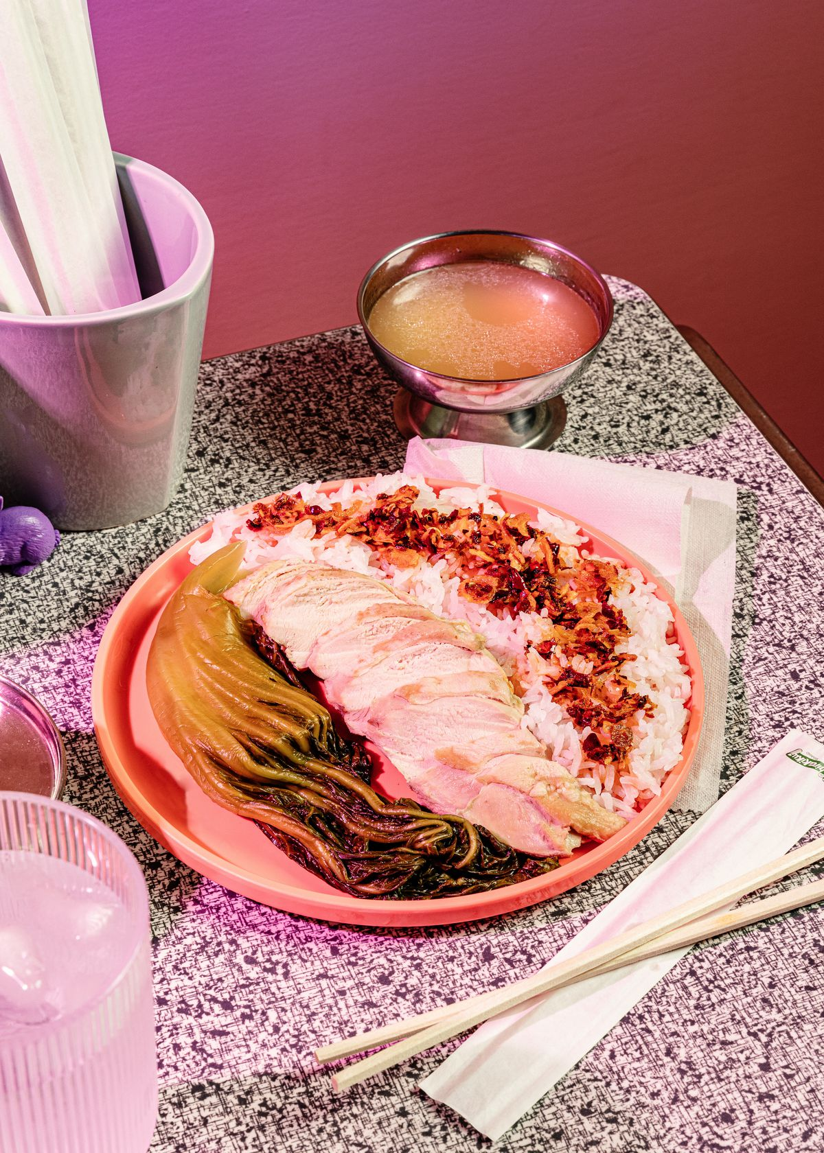 A whole piece of bok choi next to chicken and rice with a silver cup of soup on a table surrounded by wooden chopsticks.
