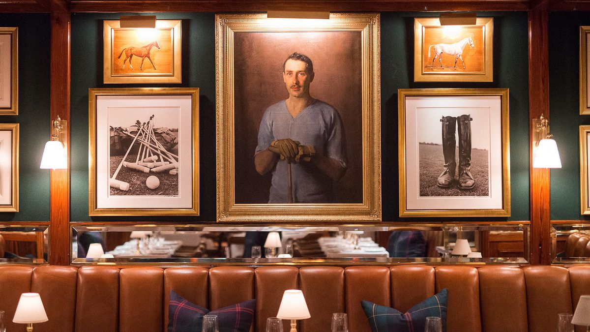 A hunter green wall has framed paintings of polo players, with a leather banquette below.