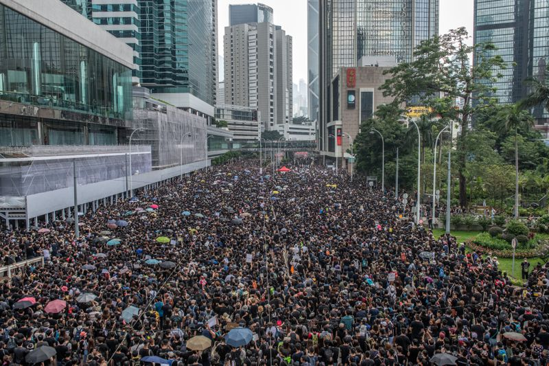 Protesters carrying umbrellas march through the streets of Hong Kong.