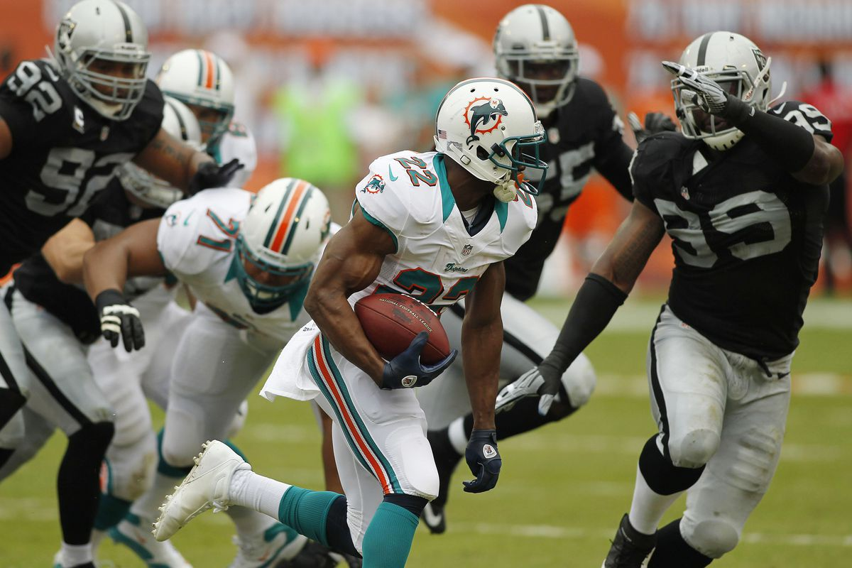 Miami Dolphins running back Reggie Bush (22) runs the ball against the Oakland Raiders in the first quarter at Sun Life Stadium.