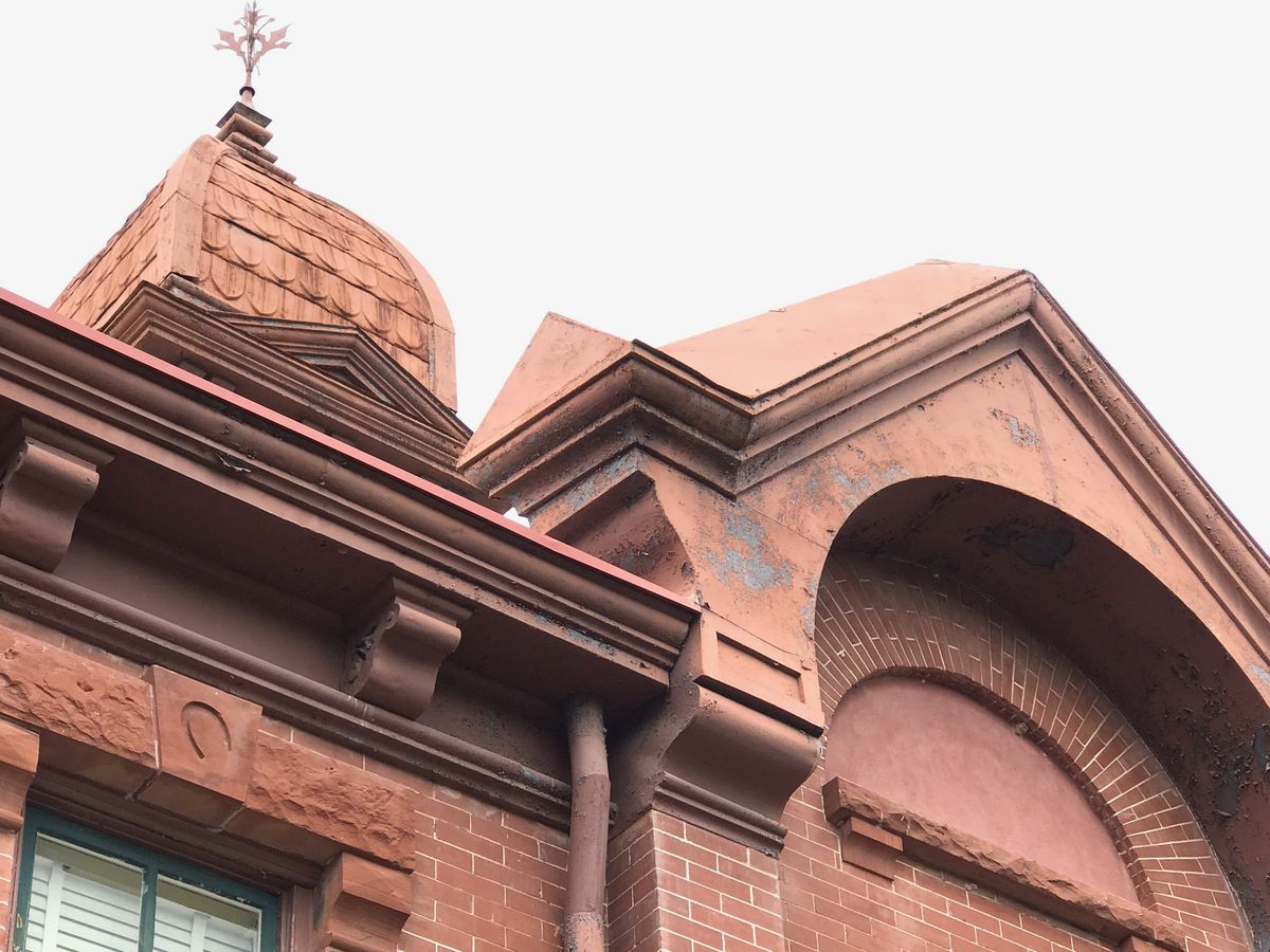 to of Red Victorian building with shingled roof and spires