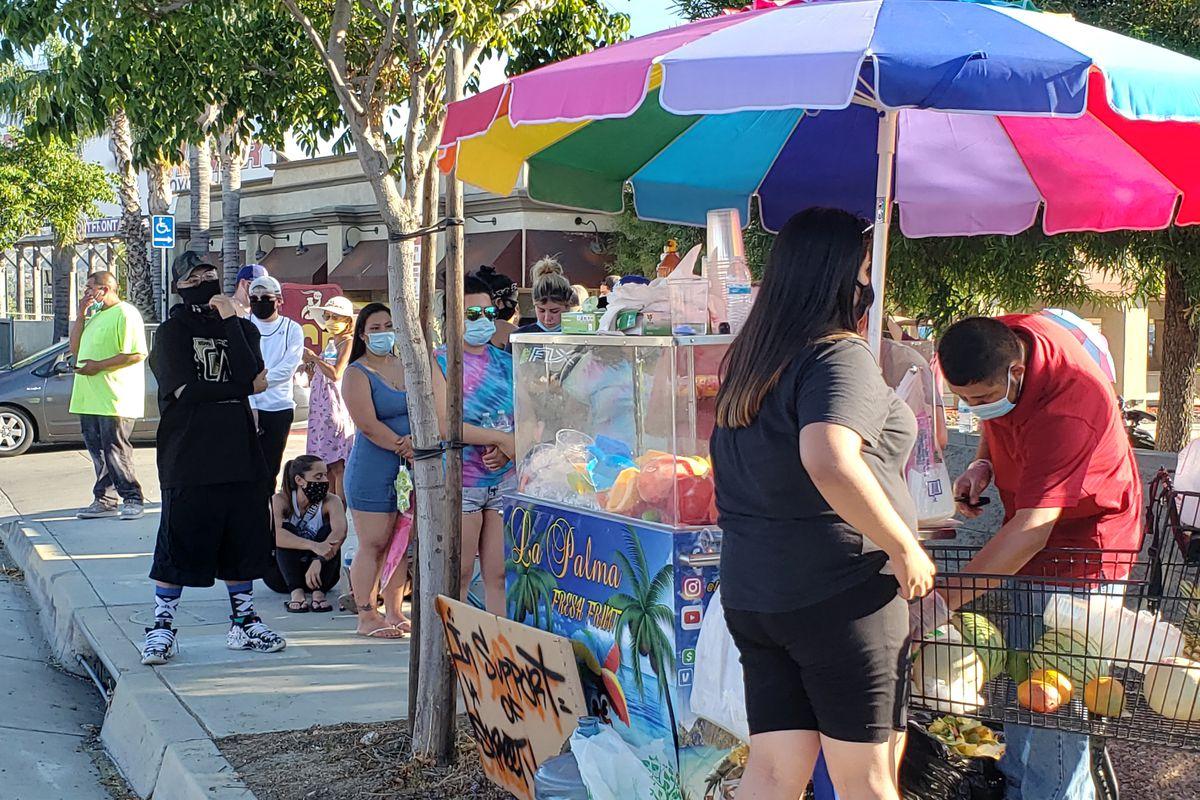 Folks wait in line for fruit and beverages at La Palma Fresh Fruit on July 13