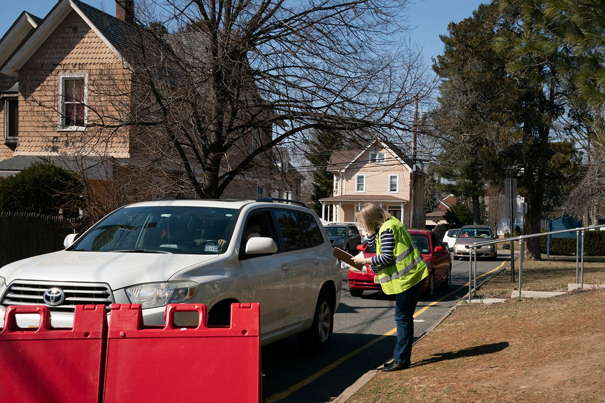 A volunteer collects information from drivers lined up to receive food boxes at the Center for Food Action in Englewood, New Jersey.