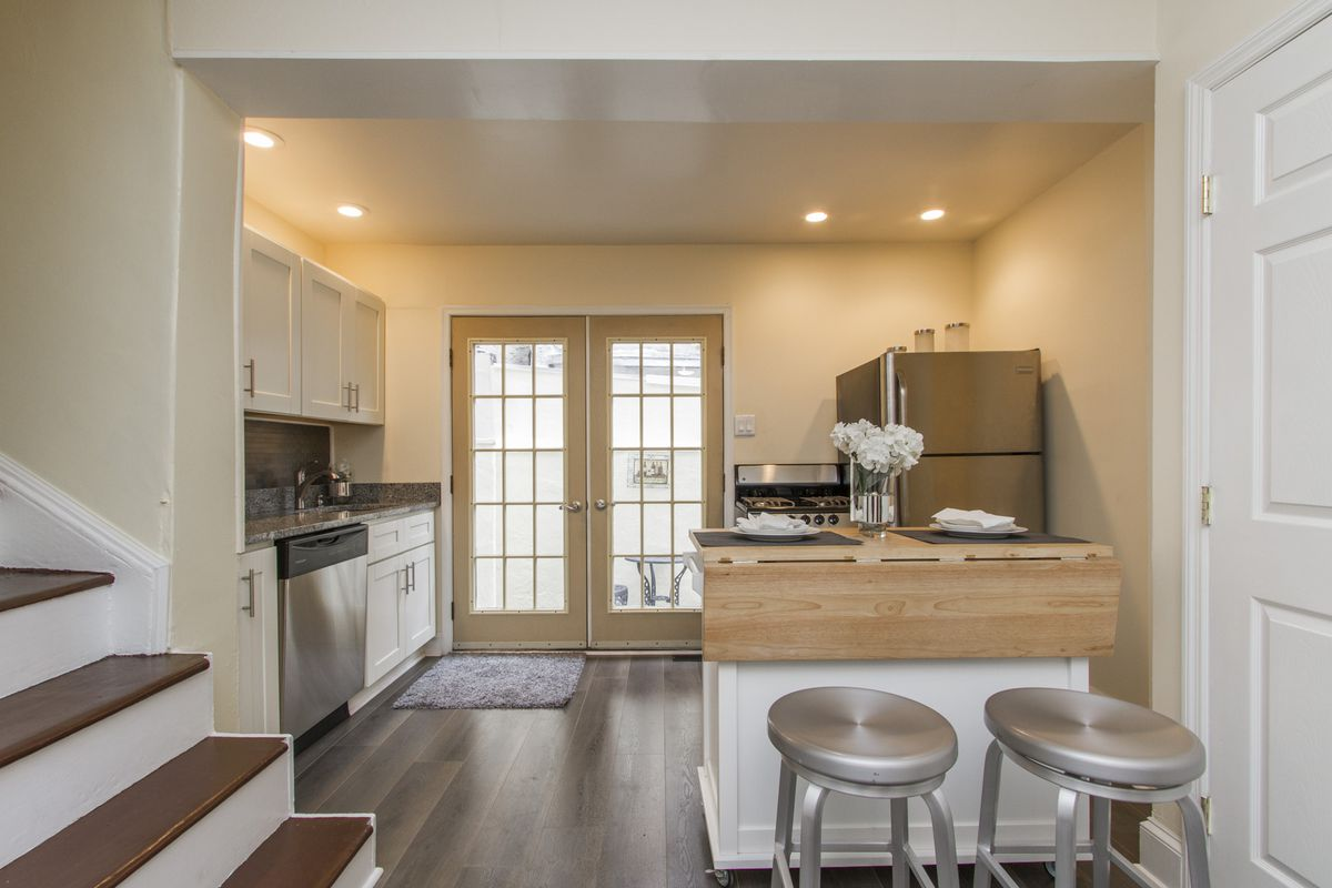 A kitchen with steel bar stools, laminate floors, and French doors.