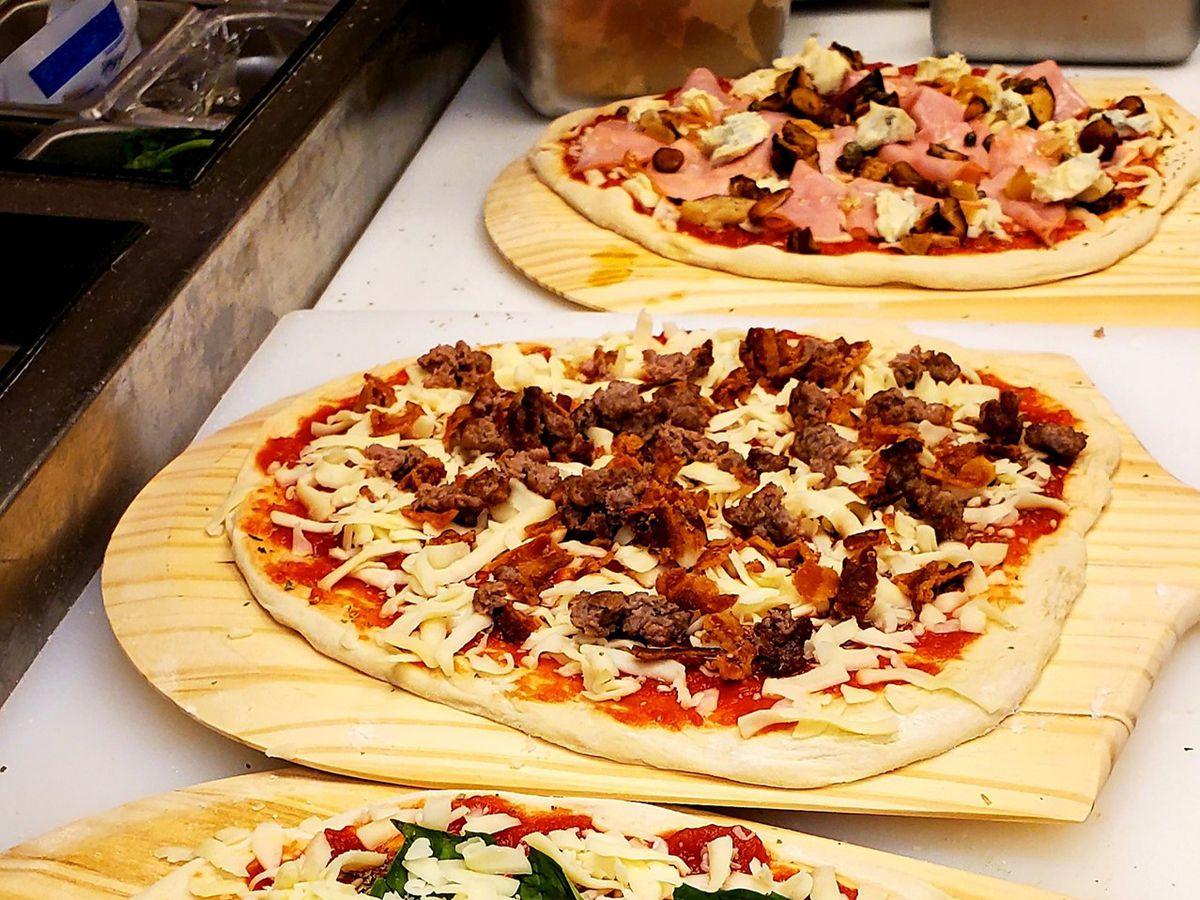 Three uncooked pizzas