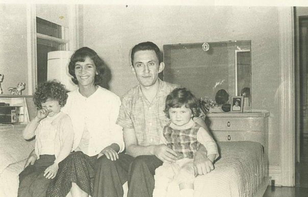 A black and white photo of a young family: two little girls on either side of a mother and father, sit together on a bed with a mirror and dresser against the wall behind them.