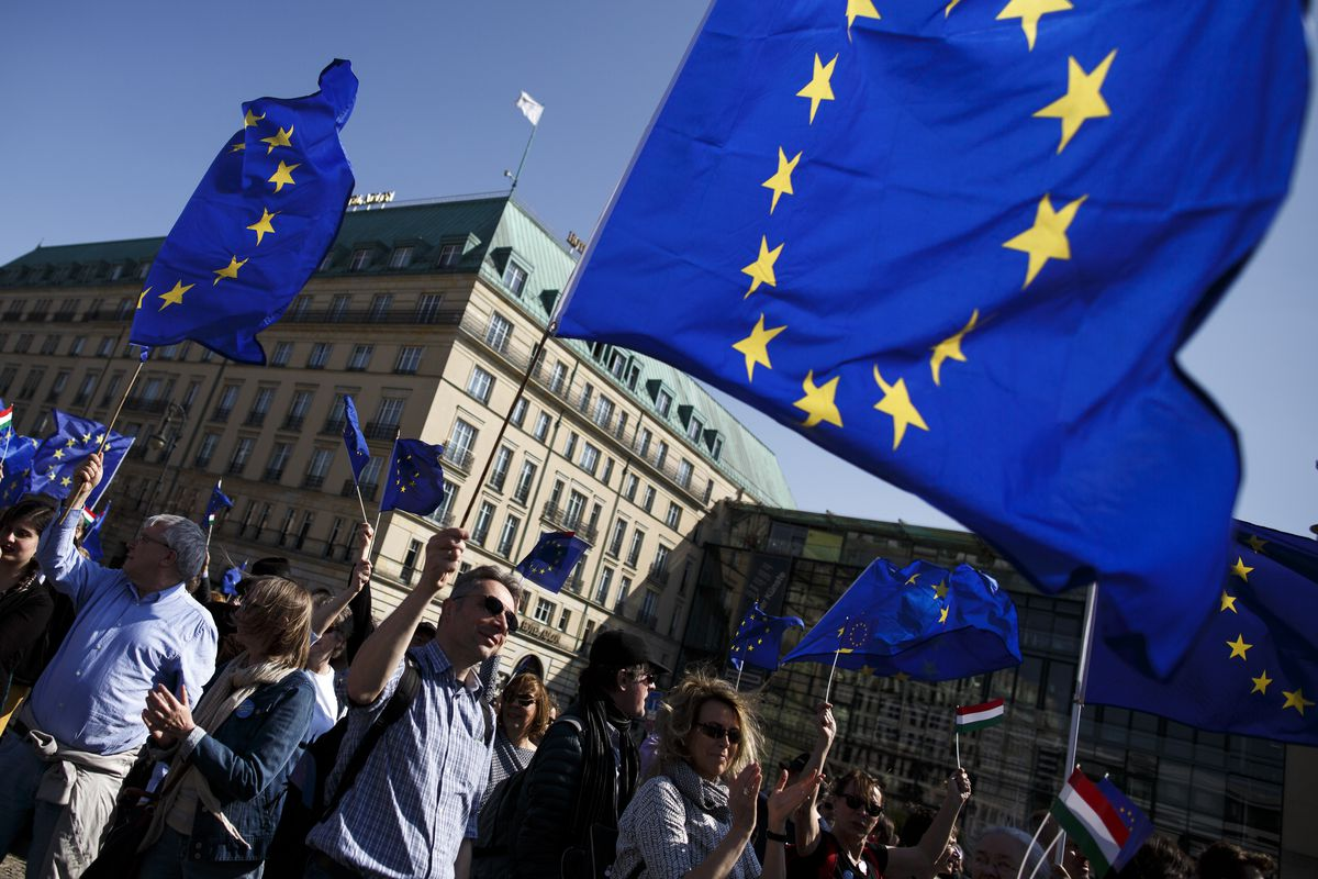 People outside the Brandenburg Gate in Berlin waving EU flags