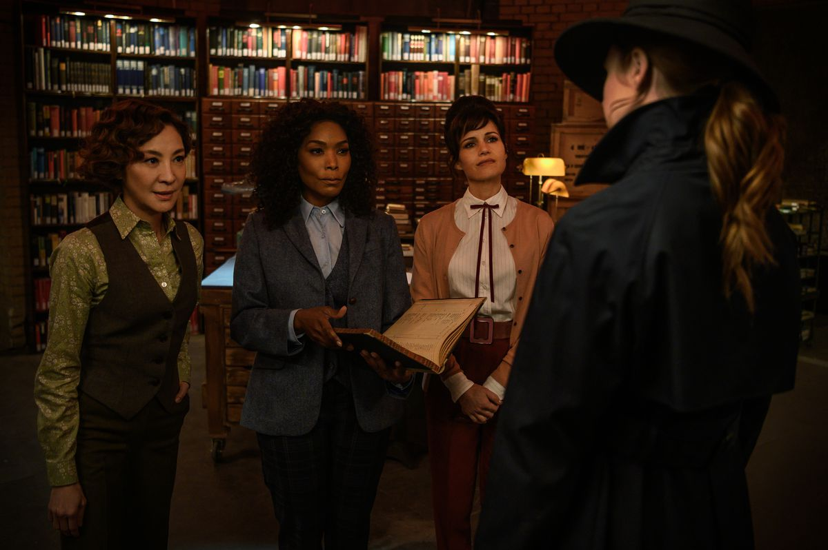 Karen Gillan, seen from behind, wearing a hat and trench coat, stands in front of a group of arms smugglers - Michelle Yeoh, Angela Bassett and Carla Gugino - in Gunpowder Milkshake