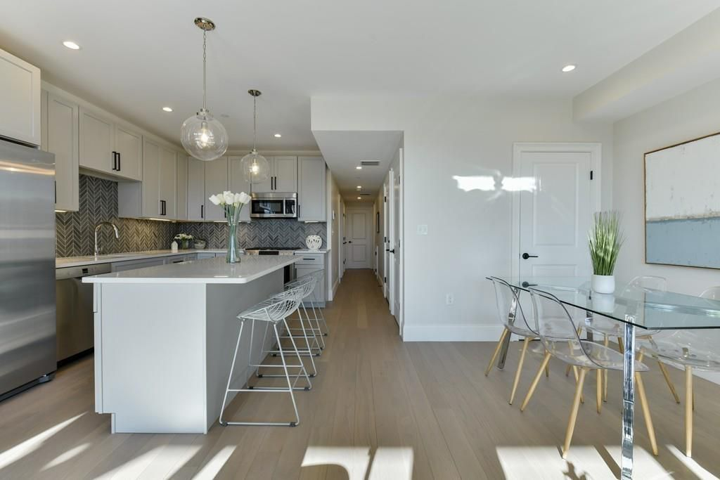An open dining room-kitchen area with an island separating the two rooms.