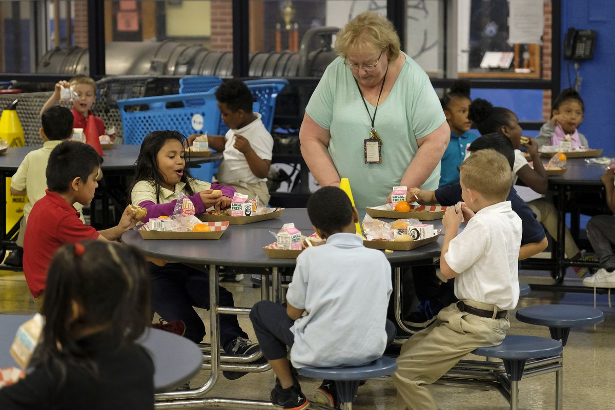 Students eat lunch as a older woman stands at their table in the cafeteria.