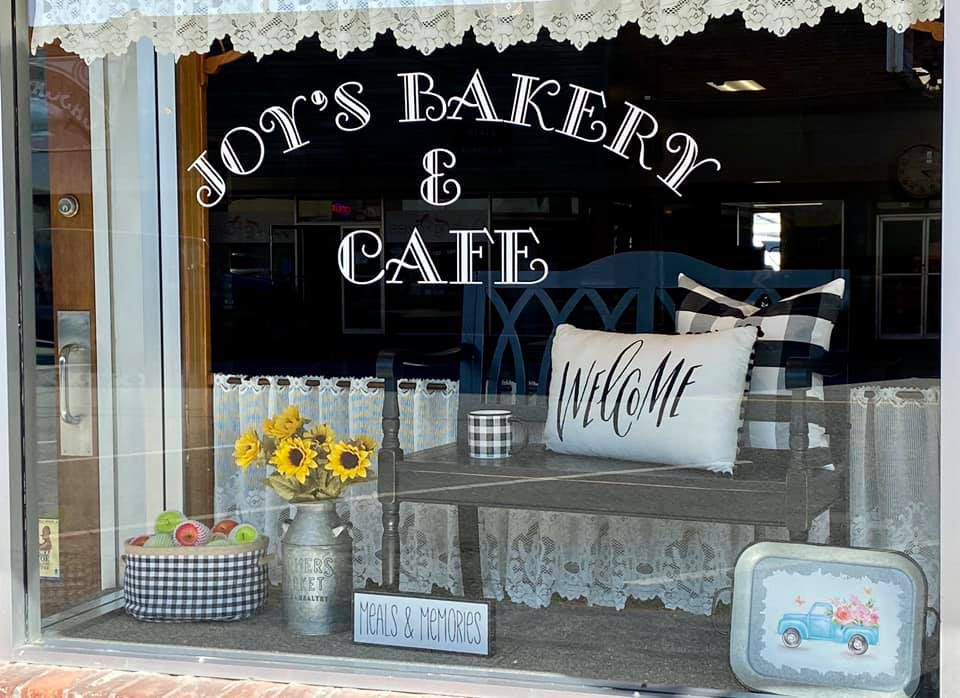 The exterior of Joy's Bakery in Sedro-Woolley, Washington, with the business's name inscribed on the window in ornate lettering, surrounded by sunflowers in a vase and a frilly curtain