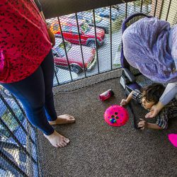 Kholoud Abou Arida, left, watches her children, Zain, 3, and Nour Bilal, 15, play at their home in Millcreek on Tuesday, Sept. 8, 2015.