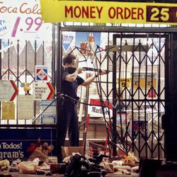 FILE - In this April 30, 1992 file photo, a Los Angeles police officer takes aim at a looter in a market at Alvarado and Beverly Boulevard in Los Angeles during the second night of rioting in the city. The acquittal of four police officers in the videotaped beating of Rodney King sparked rioting that spread across the city and into neighboring suburbs. Cars were demolished and homes and businesses were burned. Before order was restored, 55 people were dead, 2,300 injured and more than 1,500 buildings were damaged or destroyed.