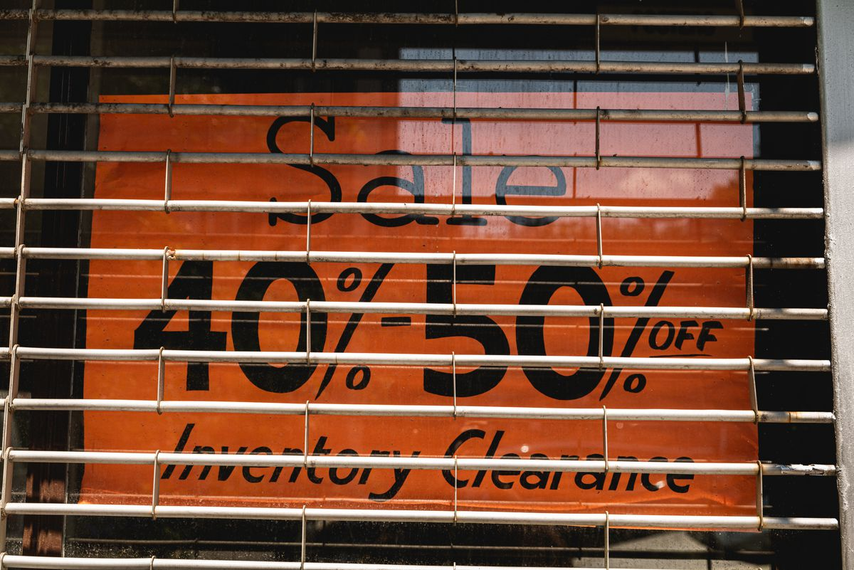 """A photo of a sign behind a store window and grate that says, """"Sale 40%–50% off Inventory Clearance."""""""