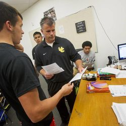 Austin Thorsen hands coach Matt Labrum an assignment as Union High School football players in Roosevelt attend a study hall and a meeting Wednesday, Sept. 25, 2013. Some players were told they wouldn't be playing in Friday's homecoming game. The football coaches at Union High in Roosevelt have taken a stand against poor performance in the classroom and bullying outside the classroom, including disrespect of teachers and students.