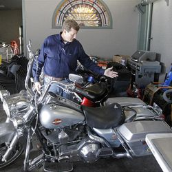 """This Oct. 17, 2012, photo shows Rob Olson of Erkelens & Olsen Auctioneers displaying Rulon Gardner's Harley-Davidson motorcycle at his auction house, in Salt Lake City. The auction of Olympic gold medalist Rulon Gardner's most valuable belongings is being postponed indefinitely as the decorated wrestler tries to buy back """"stuff that really matters to him,"""" his new bankruptcy lawyer says. A major creditor seized a Ford Excursion SUV, Harley-Davidson motorcycle, dozens of watches and knives, his wrestling shoes, autographed memorabilia and more. Gardner's gold and bronze medals are not in play; he previously put them up as collateral for personal loans. (AP Photo/Rick Bowmer)"""