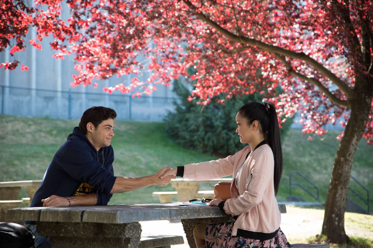 """A boy and a girl hold hands across a picnic table in the Netflix movie """"To All the Boys I've Loved Before."""""""