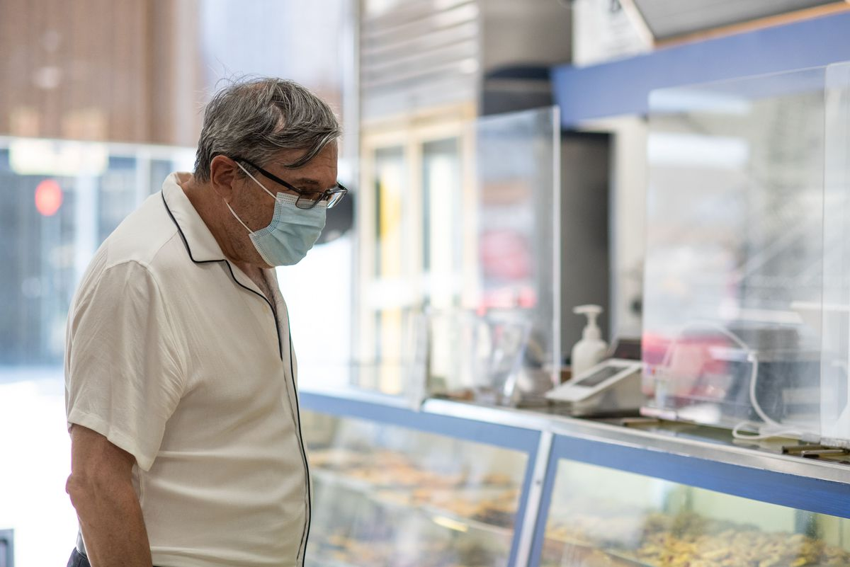 A customer in black glasses and a mask looks into a pastry case.