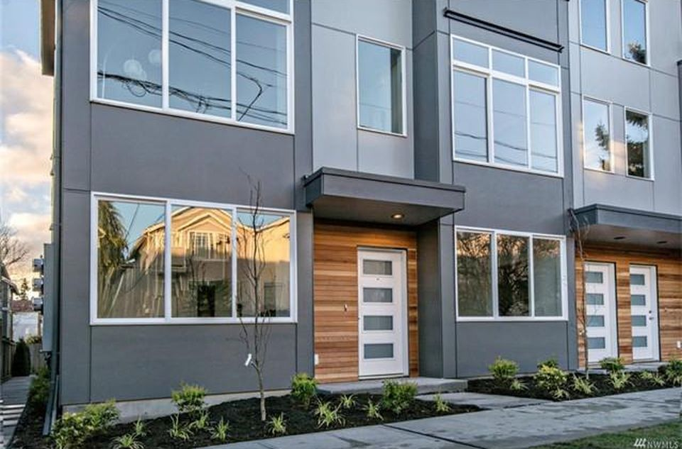 A gray townhouse with wood slatted walls around the white door.