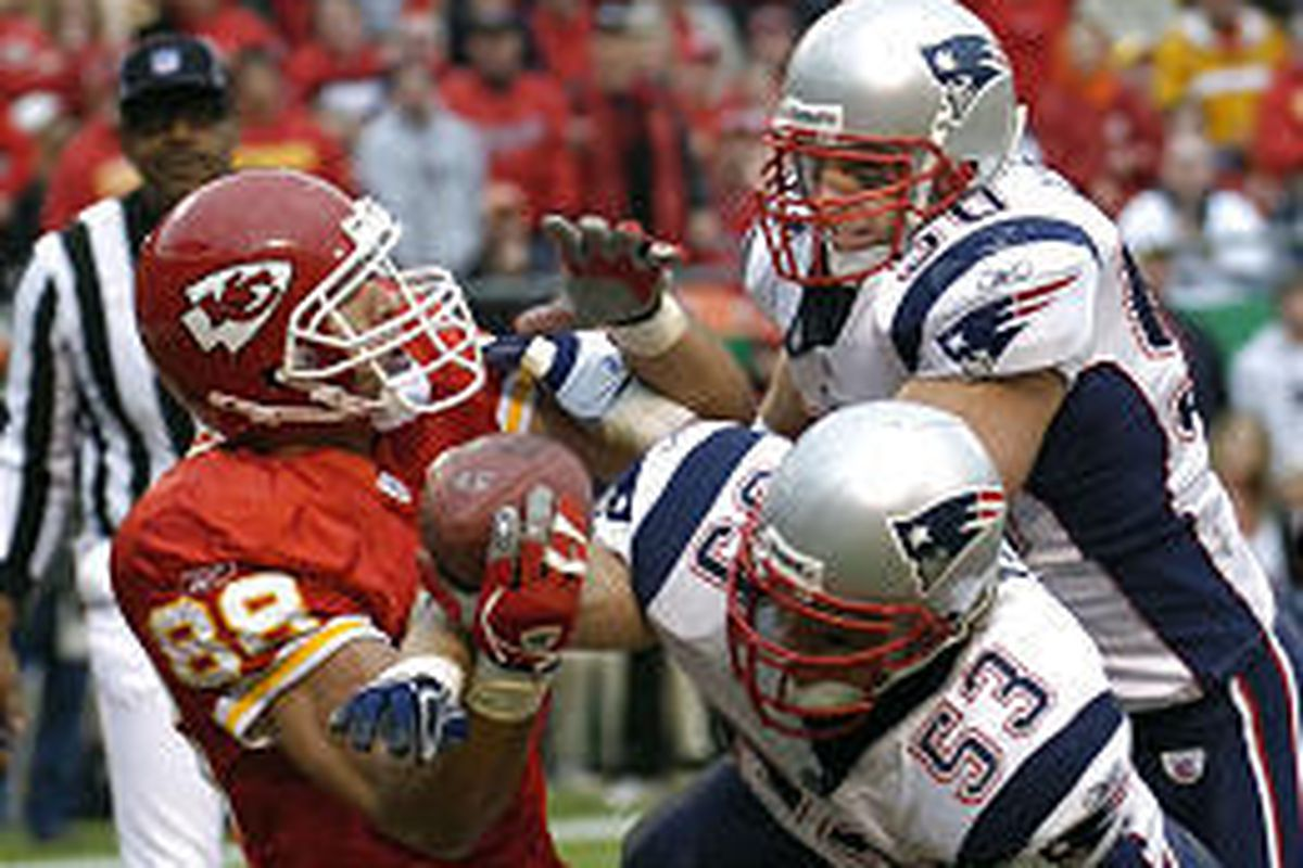Kansas City tight end Tony Gonzalez (88) has the ball knocked from his hands by New England's Larry Izzo (53) and Mike Vrabel (50).