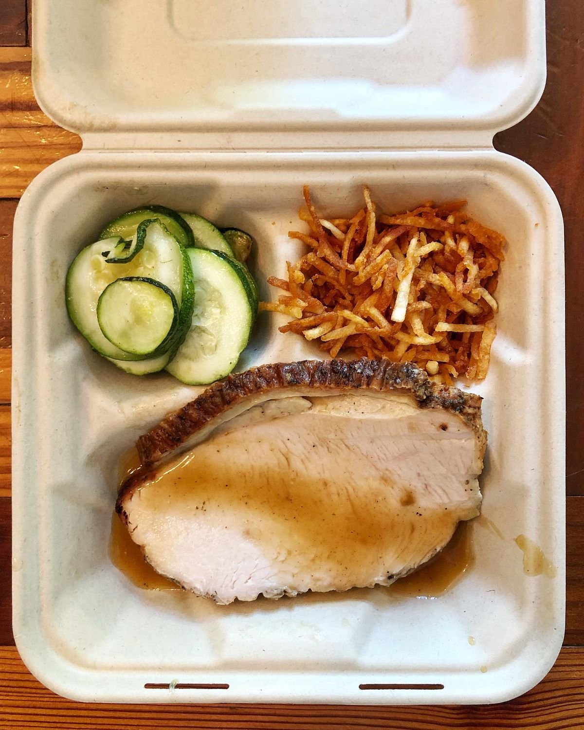 A meal for Table & Aid featuring roast turkey breast, roasted zucchini, and shoestring potatoes