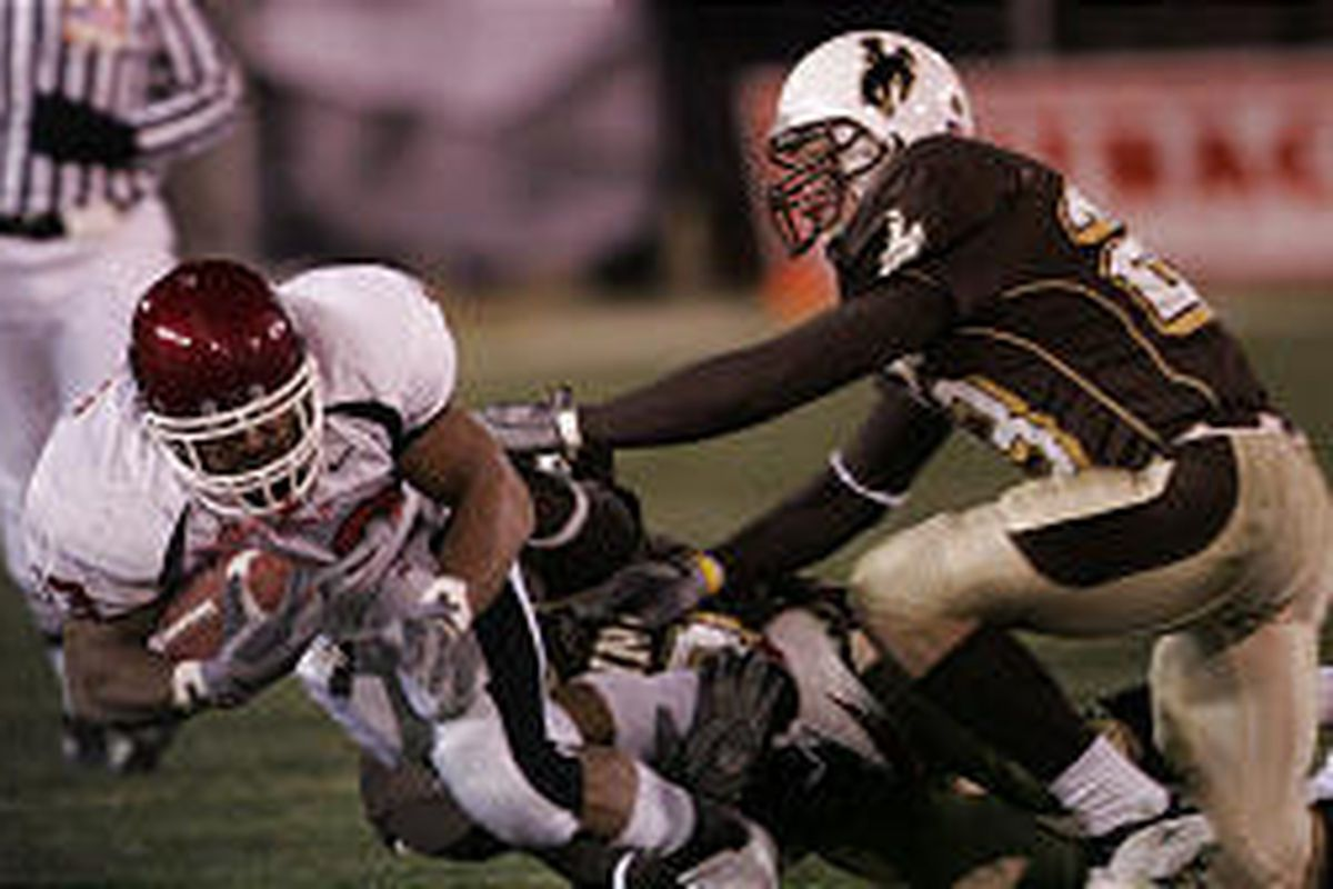 U.'s Quinton Ganther rushes for a gain against Wyoming's John Wendling. Ganther's status for Saturday's game with Wyoming is questionable.