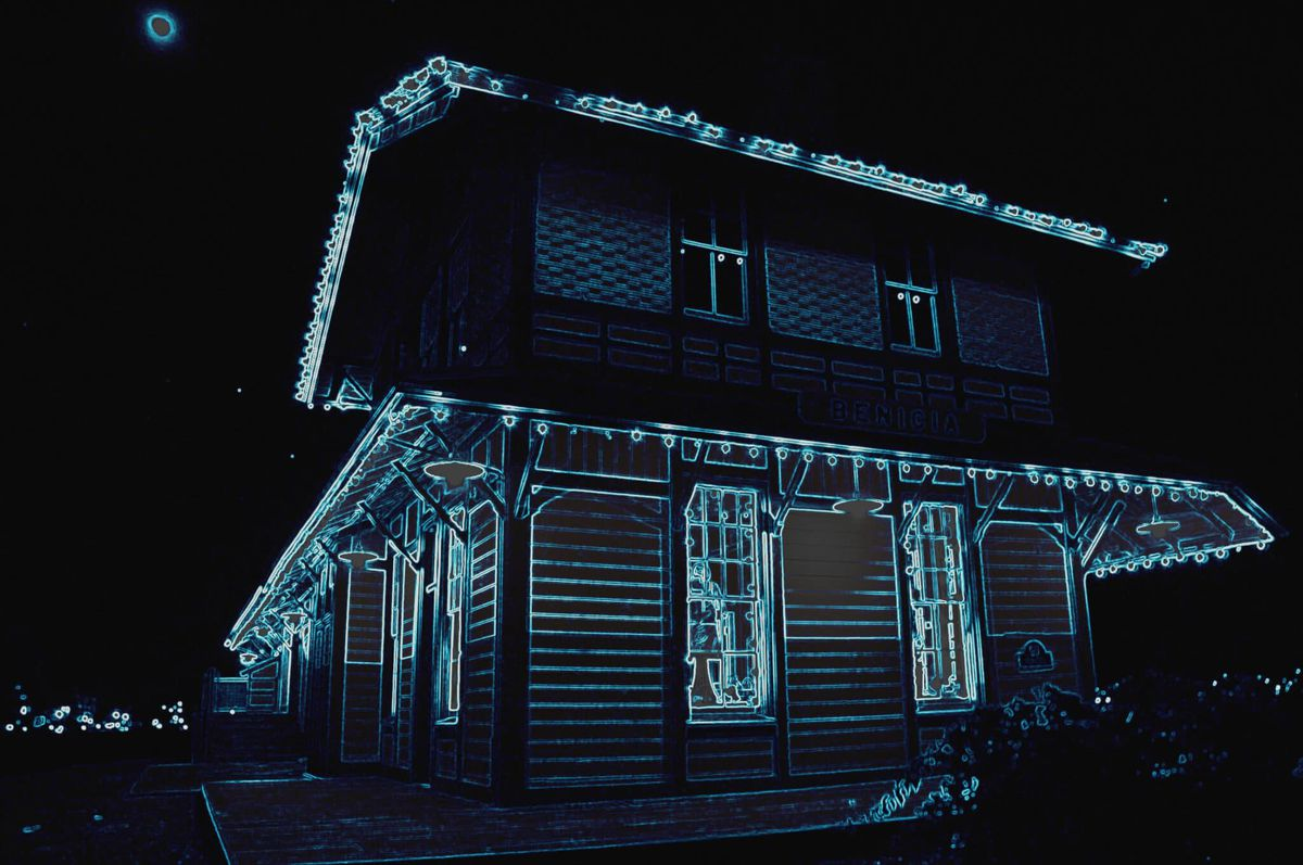 A two-story 19th century train station decorated with eerie blue lights.