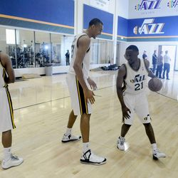 The Jazz's Ian Clark, right, has fun making his way around teammate Rudy Gobert, center, while teammate Scott Machado watches and other teammates get their photos taken during media day at the Zions Bank Basketball Center on Sept. 30.