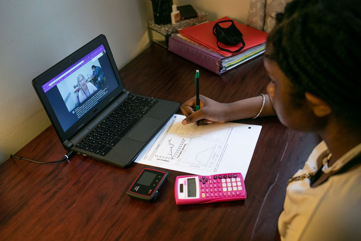 A Deaf student works with a teacher over her laptop at home. She is writing notes next to a pink calculator.