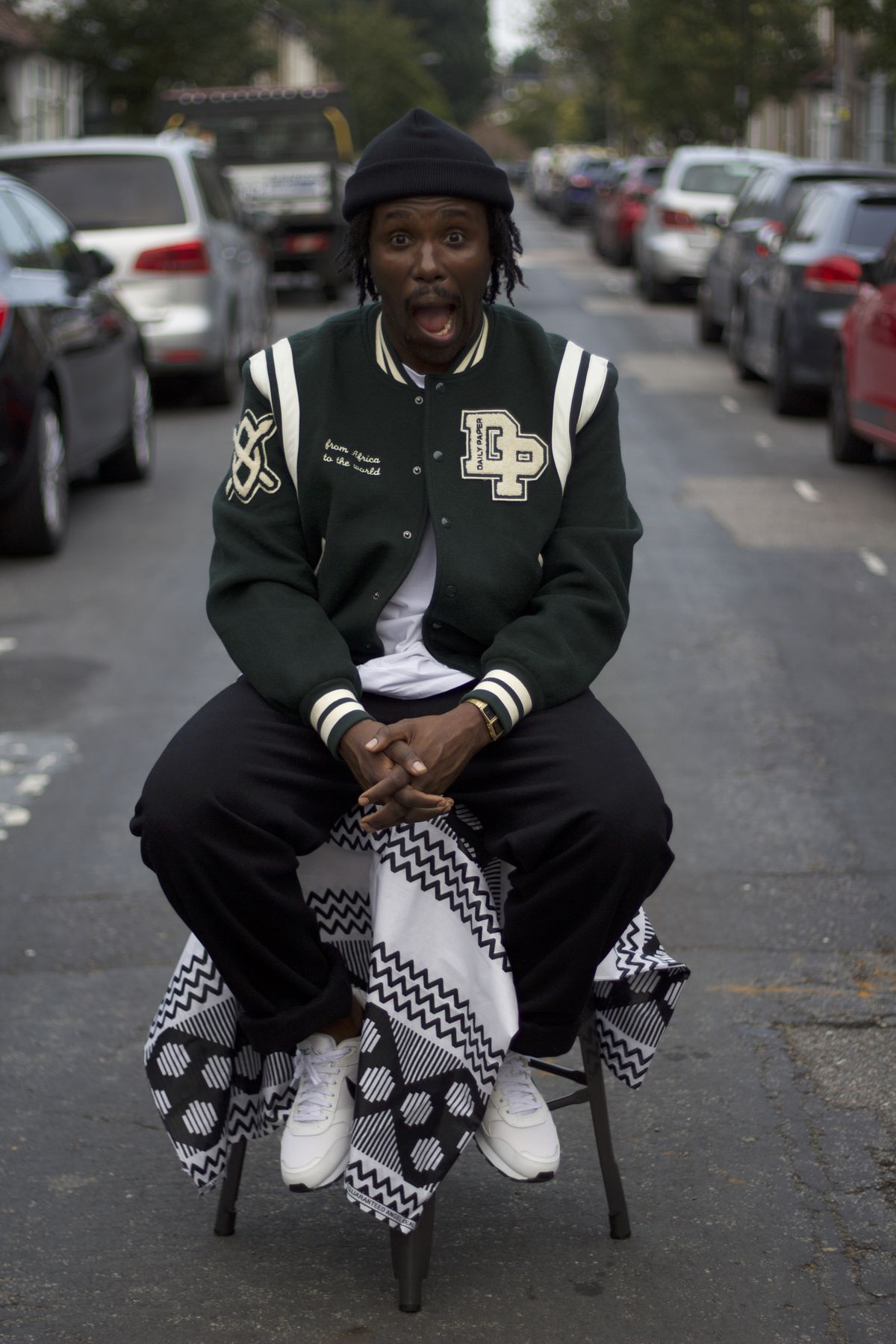 Akwasi Brenya-Mensa, smiling widely while sitting on a table in the middle of a road