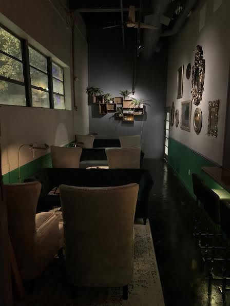 A shot of the lounge bar inside Aunty Betty's Gin & Absinthe Bar in Raleigh with silver wingback chairs and low black couches