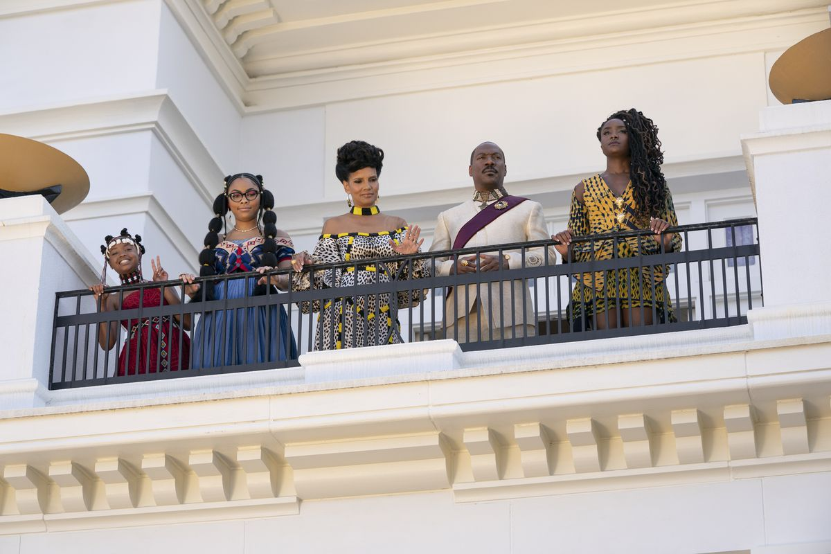Prince Azeem (Eddie Murphy) and his family, played by Akiley Love, Bella Murphy, KiKi Layne, and Shari Headley, stand on a balcony looking down in Coming 2 America