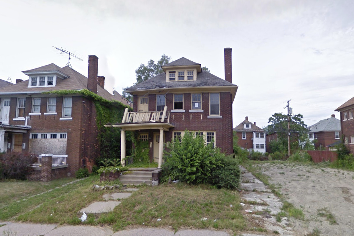 A two story brick home. There's a large untended bush outside the front windows and a wobbly porch overhang.