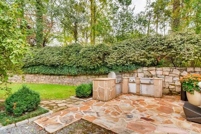 A leafy backyard with a kitchen built of stone.