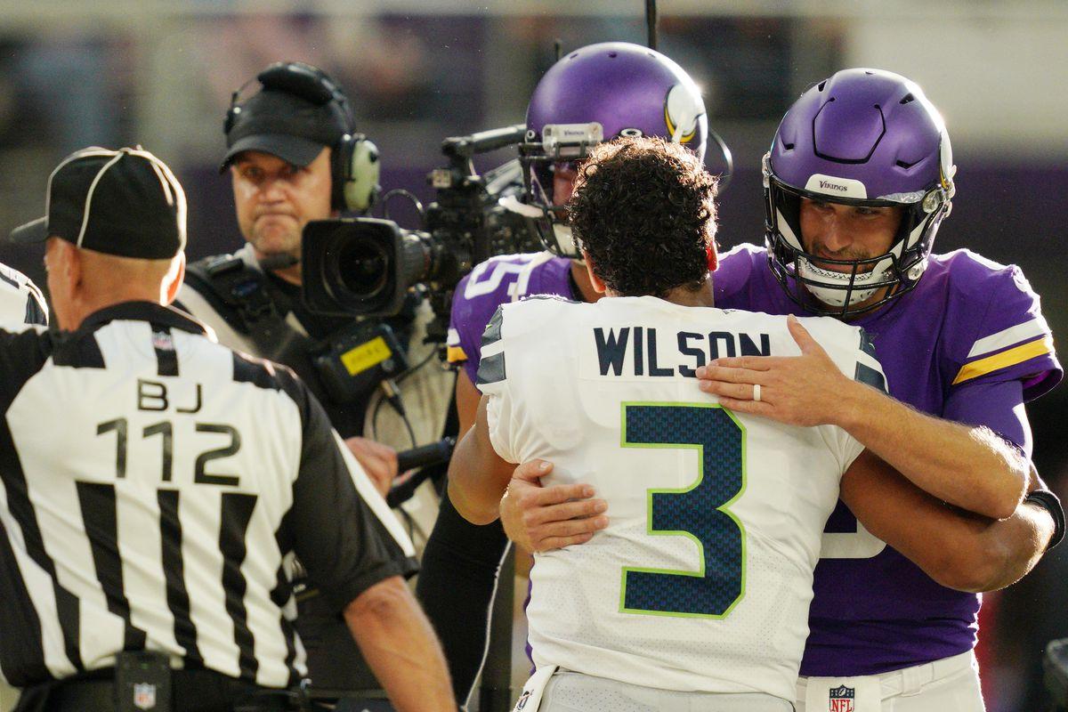 Minnesota Vikingsquarterback Kirk Cousins and Seattle Seahawks quarterback Russell Wilson hug at the end of an NFL preseason football game.