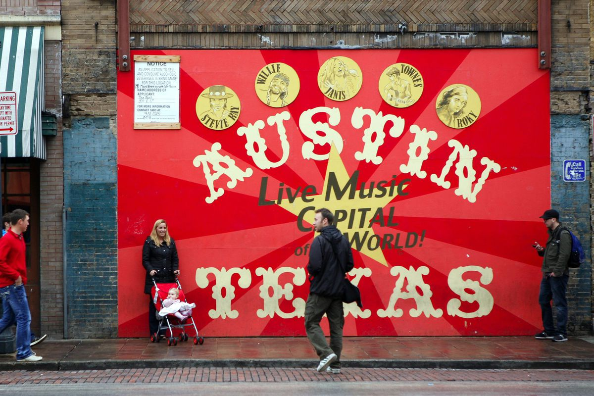 """Circus-y looking bright red mural that reads """"Austin Texas Live Music Capital of the World"""