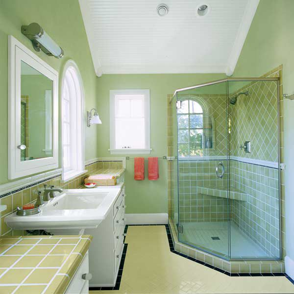 Green colored bathroom walls with extra storage space in the form of dresser drawers.