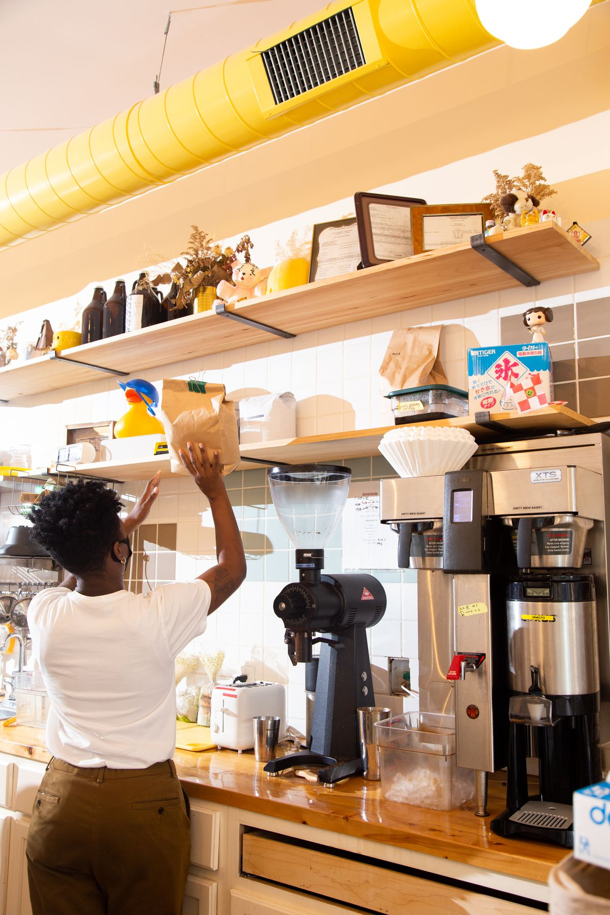 a person in a white tee shirt and brown pants lifts a brown bag onto a shelf at a coffee shop