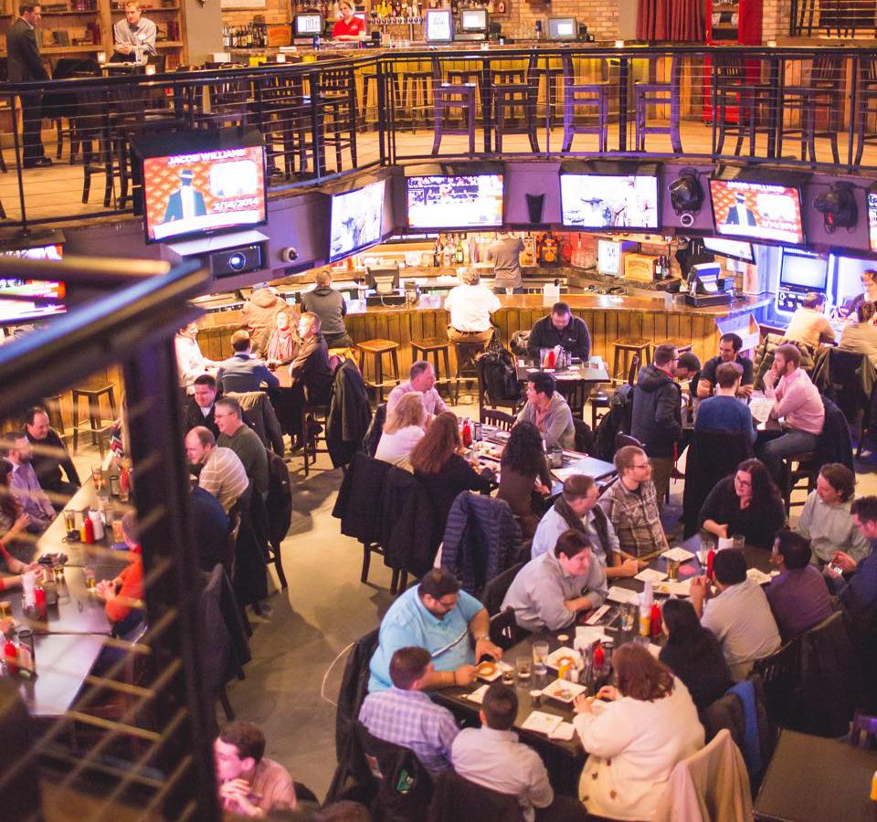 The packed, round room bar is surrounded by blinking TVs