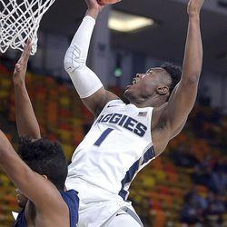 Utah State guard Koby McEwen (1) drives to the basket as Life Pacific guard Mark Eden (2) defends during an NCAA basketball game, Saturday, Dec. 16, 2017, in Logan, Utah. (Eli Lucero/Herald Journal via AP)