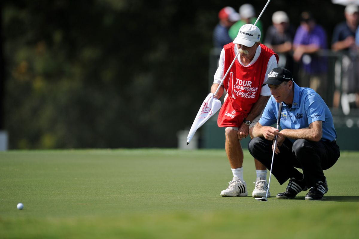 Sep 21, 2012; Atlanta, GA, USA; Jim Furyk (USA) (in blue) and his caddie Mike Cowan on the 12th green during the second round of the TOUR Championship at East Lake Golf Club. Mandatory Credit: Kevin Liles-US PRESSWIRE